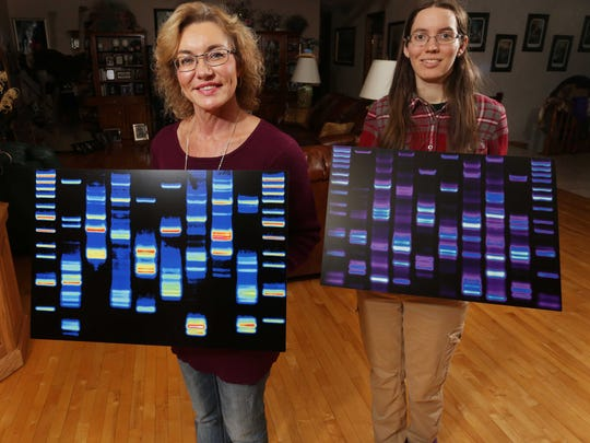 Cheryl Briggs, left, and daughter, Amy, hold maps of their DNA.