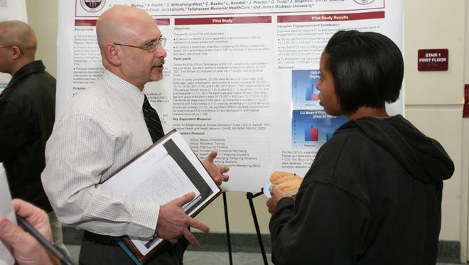 FSU professor Rob Glueckauf, who is leading a project on relieving stress of caregivers,  talks to student.