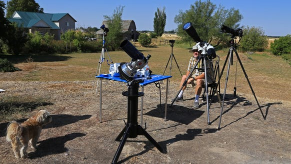 St. George resident Quinn Passey sits among his telescopes
