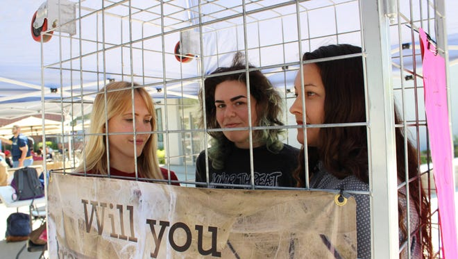 """Stephanie Bain stands with two Fresno State students inside the life-size """"battery cage"""" as they experience what life is like for 95% of hens on California egg farms."""