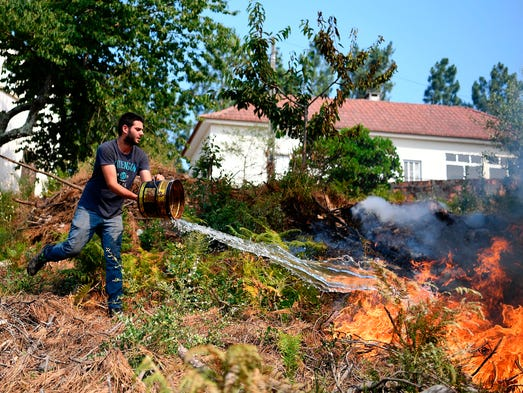 Locals use buckets trying to extinguish a wildfire