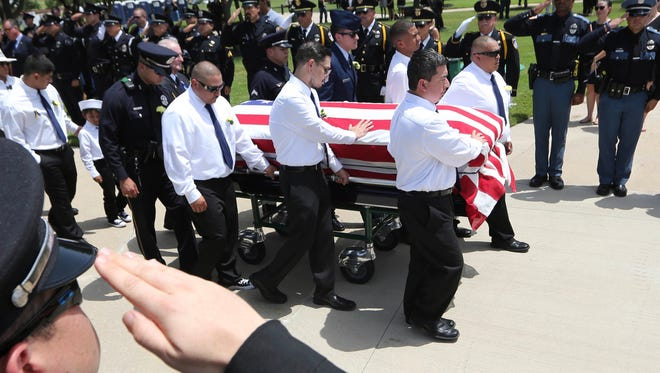 Pallbearers lead the flag-draped coffin of slain Dallas police officer Patrick Zamarripa at Dallas-Fort Worth National Cemetery on July 16, 2016.