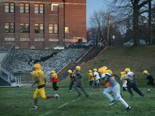 Howe High School football players warm up on the field during practice at the school at 4900 Julian Ave., Indianapolis, on Wednesday, Nov. 5, 2014. After their 20-13 win over the South Decatur Cougars, the Hornets advance to their first sectional championship football game in school history.