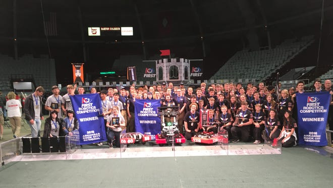 The Bomb Squad, center, poses for a picture with its alliance partners The Pioneers, left, and Black Hawk Robotics on Saturday after they won the Rock City Regional robotics competition. All three teams have earned bids to compete in the world championship to be held in April.