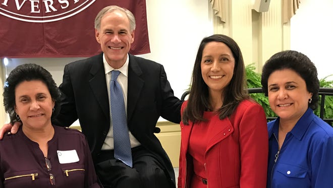 Texas Gov. Greg Abbott poses with Ginger Kerrick and her twin sisters, Velia and Delia.