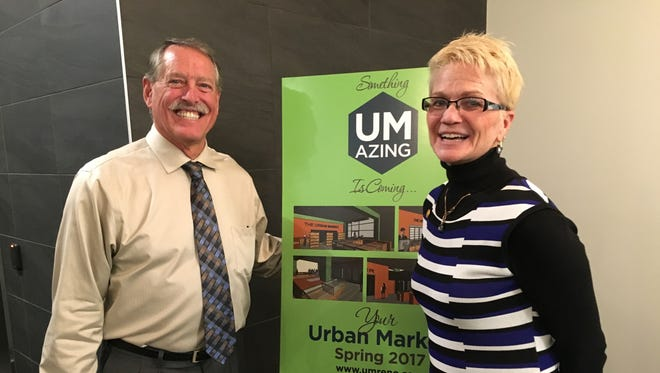 Dale and Denise Barcomb, owners of The Urban Market, pose in front of renderings at the grand opening of 3rd Street Flats, a new apartment in downtown Reno, Jan. 2, 2017