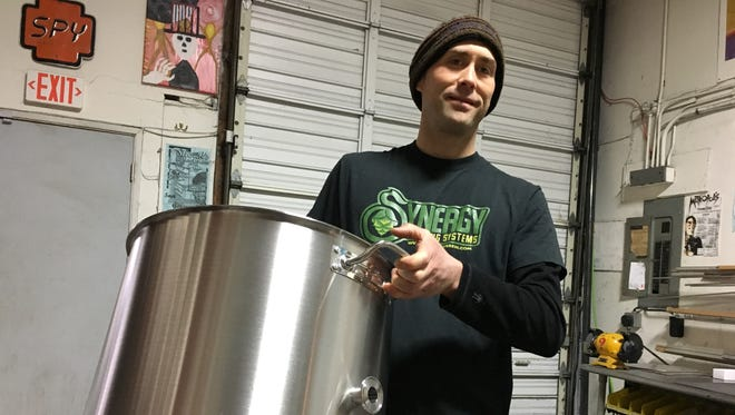 In this Feb. 7, 2017 photo, Aaron Keeney, founder and co-owner of Synergy Brewing Systems holds a stainless steel brewing kettle in Eugene, Ore. The company produces high-end home brewing systems, used by home brewers and start-up commercial brewers.