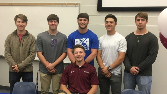 Thomas (seated) celebrates with his West Ouachita teammates after signing with Centenary College