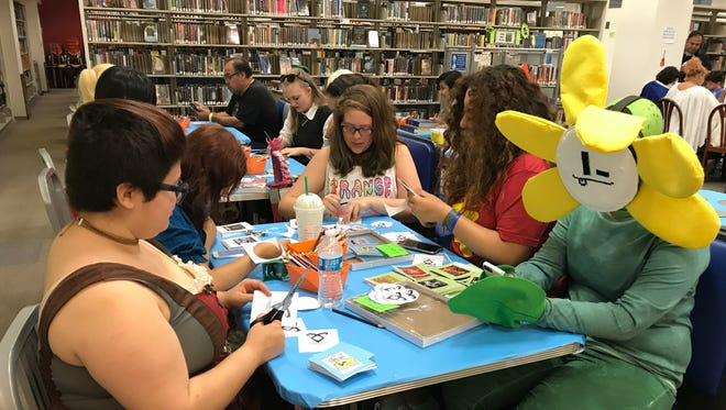 """A group of teenagers sing """"Hamilton"""" songs and make literary-related buttons at the Celebrate Books, Art and Music Event Saturday, April 29, 2017, at La Retama Central Library."""