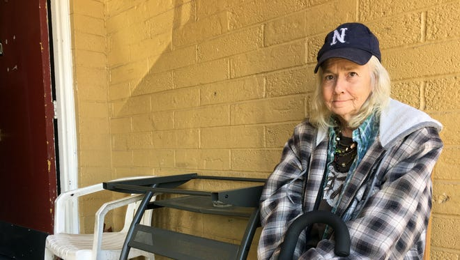 Kathy Davies poses for an environmental portrait outside of her new motel room at the Town House Motor Lodge on Second Street and Arlington Avenue. She was displaced here by the Jacobs Entertainment purchase of her former home, the Carriage Inn.