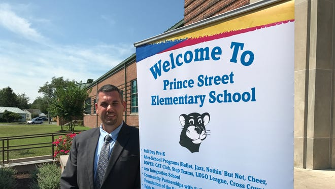 Jason Miller, Prince Street Elementary principal, stands for a portrait in front of the school on July 10, 2017.