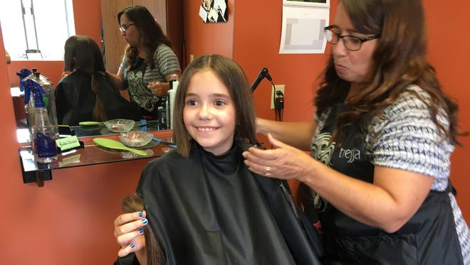 Maggie Jensen, 9, has her hair cut by Annette Hossler of a Touch of Class salon. She is donating her locks to Wigs for Kids.