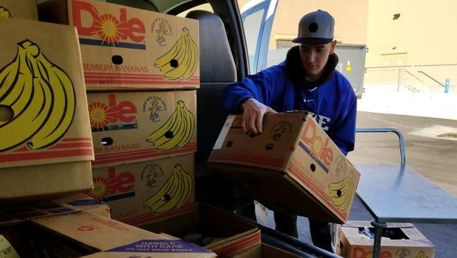 SVDP volunteer Tyler Faulk picks up fresh produce from the new Wal-Mart.