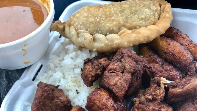 A plate of fried pork with rice, beans, sweet plantains and a beef empanada (all for less than $10) from the Famous Corner food truck in Cape Coral.