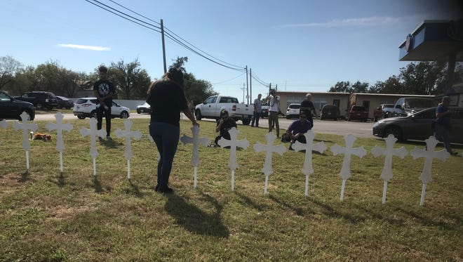 Sheree Rumph of San Antonio praying over 26 white metal crosses set up in front of the VP Racing Fuels convenience store