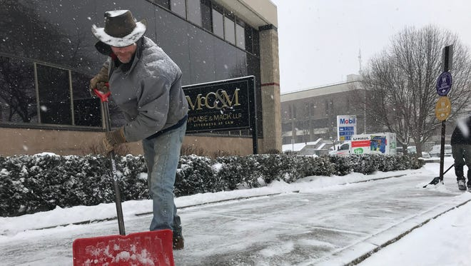 Glenn Reed of Stanfordville clears snow from the sidewalk on Washington Street in the City of Poughkeepsie on Wednesday