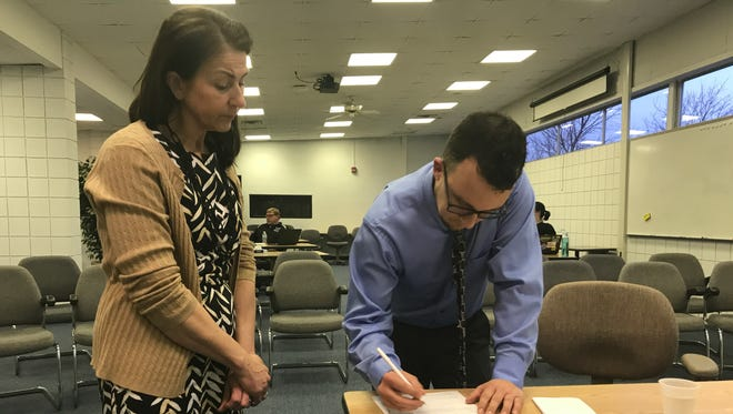 New Harper Creek Community Schools Board of Education member Gary Baker signs the acceptance and oath of office form as Superintendent Rob Ridgeway's executive assistant Sharon Zebell looks on Monday.