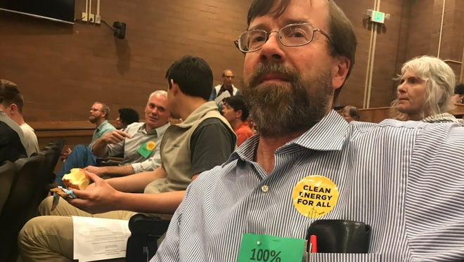 Kevin Cross, an organizer with the Fort Collins Sustainability Group, shows off the green placard he and others wore to call for 100 percent renewable energy sources by 2030 at a recent city council meeting.