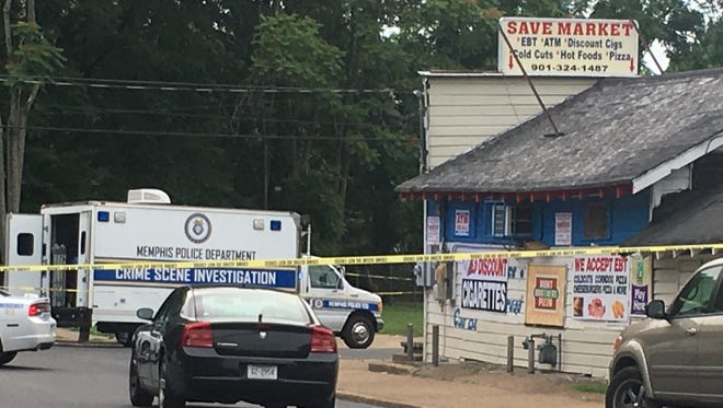 A crime scene investigation van is parked near Save Market on Oakwood Street following a fatal shooting on May 23, 2018.