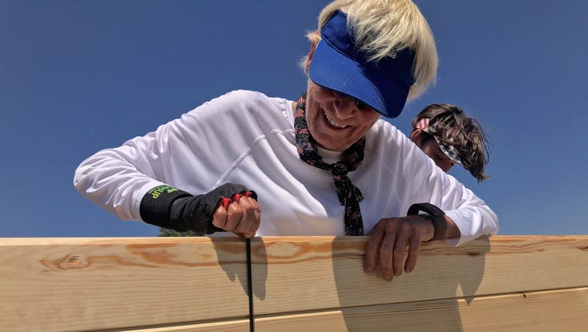 Lynn Dorgan shows one of the 1,500 screws being used to construct the tiny house. Once completed, the home will be sold, with proceeds going to the Ojai-based equine-therapy program, Reins of H.O.P.E.
