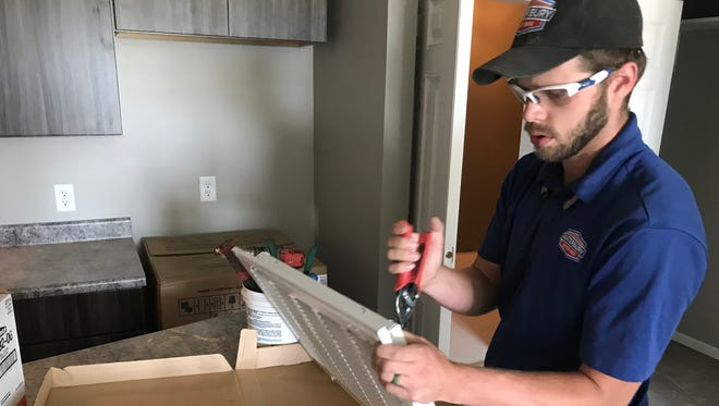 Ethan Thompson with Waterbury Heating and Cooling Inc. works on a vent cover in the Copper Pass apartments, still under construction in eastern Sioux Falls. Copper Pass is pre-certified to meet Passive House energy efficiency standards.
