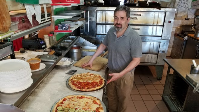 "Mario Mennella, the owner of Buona Pizza, looks over two of the countless pizzas he's prepared inside the Bernardsville eatery.  ""I started making pizzas when I was 5 or 6,"" said Mennella, 50.  His father founded Buona Pizza in 1970 and still helps make some of the items."