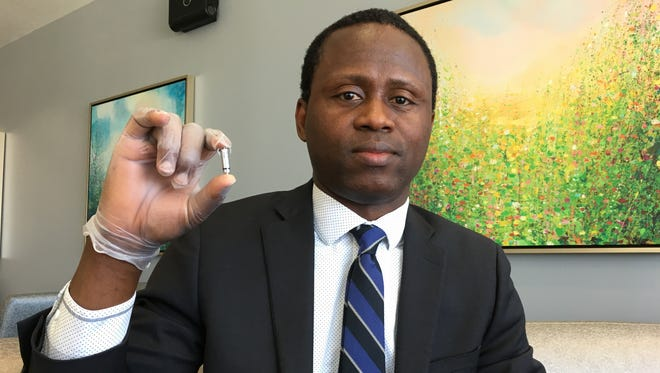 Dr. Lookman Lawal holds the Micra pacemaker, the tiniest pacemaker available.