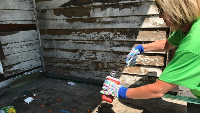 Kara Izzo, a volunteer with Find Your Path in Rochester, collects used needles behind an abandoned house.