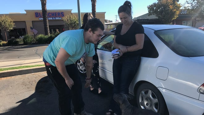 Milynn Pirro, left, and her son, Chris Rathja, wait in the parking lot of the La Quinta Inn & Suites in Redding on Monday. The family was displaced by the Camp Fire in Butte County and had to come to Shasta County to find lodging.