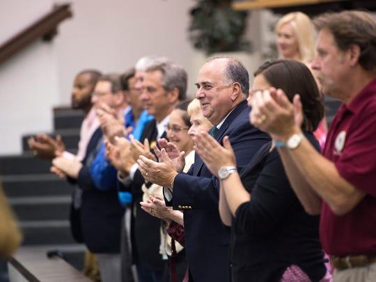 People stand and applaud after Binghamton Mayor Richard
