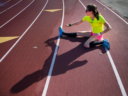Kimberly Ruck, a member of the Greenville Track Club Elite team, stretches after completing training on the track at Furman University on Wednesday, December 7, 2016.