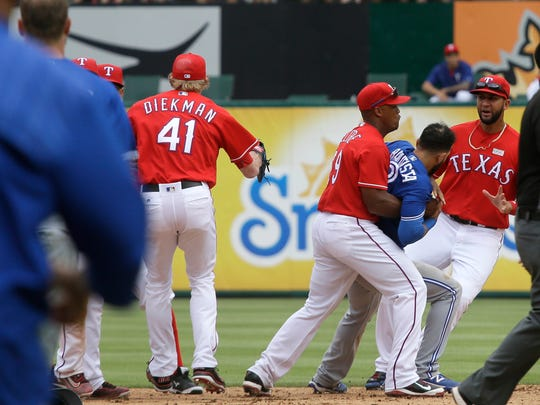 Texas Rangers third baseman Adrian Beltre (29) holds onto Toronto Blue Jays right fielder Jose Bautista (19) during  a fight in the eighth inning of a baseball game in Arlington, Texas, Sunday, May 15, 2016.