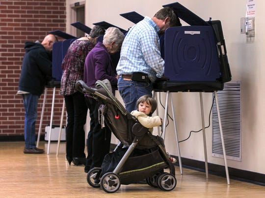 Young George Burgess looks toward the poll manager help table while his father, Darrell Burgess of Anderson, votes in a 2016 election at Central Presbyterian Church in Anderson.