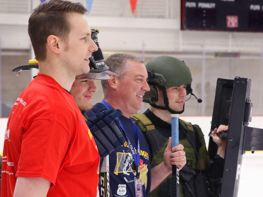 Steve Dufek of the West Allis Fire Department (front), Admirals forward Tyler Moy, Mike McDermott of the Wauwatosa Police Department and Admirals goalie Jake Paterson pose for a promotional photo for the Battle of the Badges hockey game between area police and fire departments personnel at the Panther Arena on March 4.