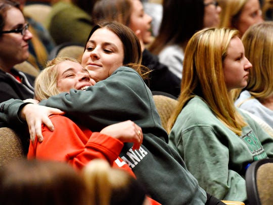 Lindsay Dowdy, left, is quickly hugged by her neighbor