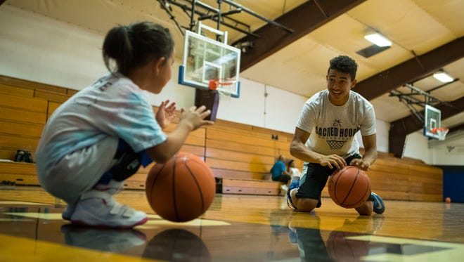 Alejandro Rama, 17, does basketball drills with Gracie Banks, 5, at Red Cloud High School on the Pine Ridge reservation Monday, July 16, 2018.