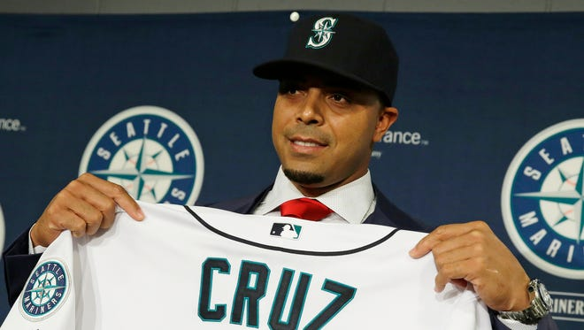 Nelson Cruz poses for photos as he displays his new Seattle Mariners jersey after he was officially introduced by the team in Seattle. Cruz goes through his first workout on Wednesday, Feb. 25, 2015,  as the Mariners hold their first full squad workout.