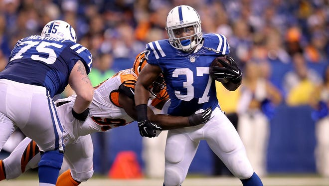 Indianapolis Colts running back Zurlon Tipton (37) attempts to run away from Cincinnati Bengals defensive end Will Clarke (93) in the second half of the AFC Wild Card game on Sunday, January 4, 2015, at Lucas Oil Stadium. Tipton died Tuesday in an accidental shooting.