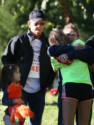 Sheri Bradway hugs her granddaughter, Sierra Bradway, at the gravesite of Indianapolis Metropolitan Police Department officer Rod Bradway at Crown Hill Cemetery. Her husband, Tom, and granddaughter Ella Bradway, 5, look on. The Bradway family was at the cemetery Sunday for Beyond the Badge 5K Run and Walk, which honors fallen public safety officers.