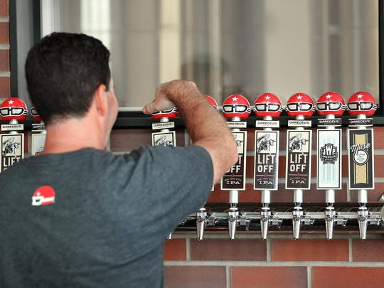 Daredevil Brewing Co co-owner Shane Pearson attaches taps at the brewery.