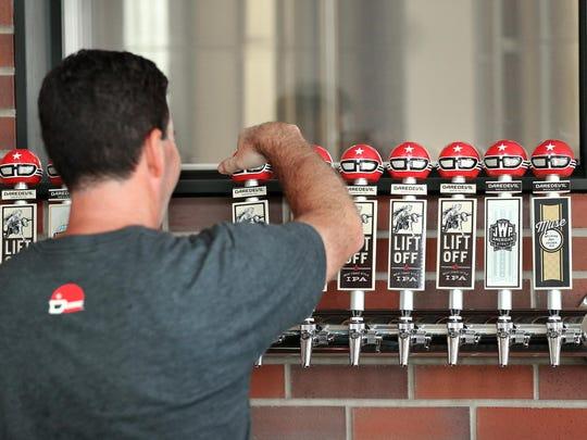 Daredevil Brewing Co co-owner Shane Pearson attaches