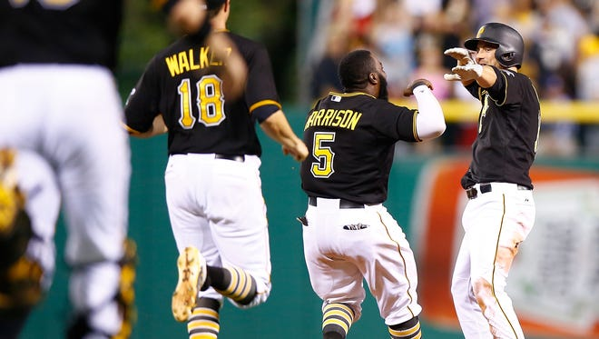 Jordy Mercer #10 of the Pittsburgh Pirates is congratulated by teammates Josh Harrison #5 and Neil Walker #18 after hitting the game winning walk off RBI single in the 10th inning against the Atlanta Braves during the game at PNC Park on June 26, 2015 in Pittsburgh, Pennsylvania.