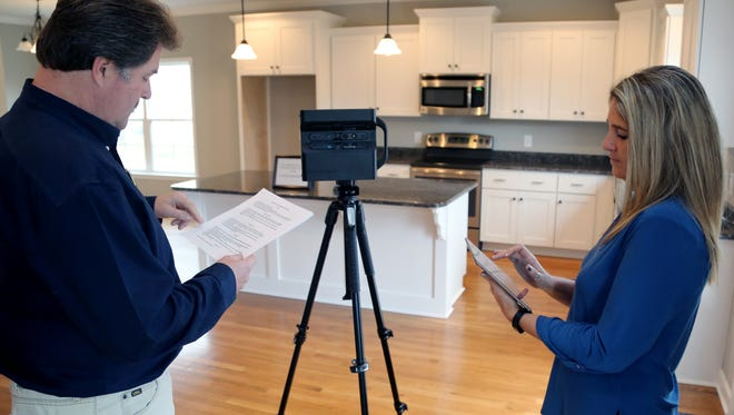 Tawny King, right, principal broker at Exit Realty in Spring Hill and Van Woody, an agent with Exit Realty and an onsite agent with John Maher Builders Inc., set up a virtual reality camera to create a 3-D video of a new home in Spring Hill.