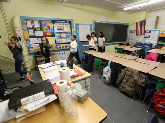 Students leave a basement classroom in the 112-year