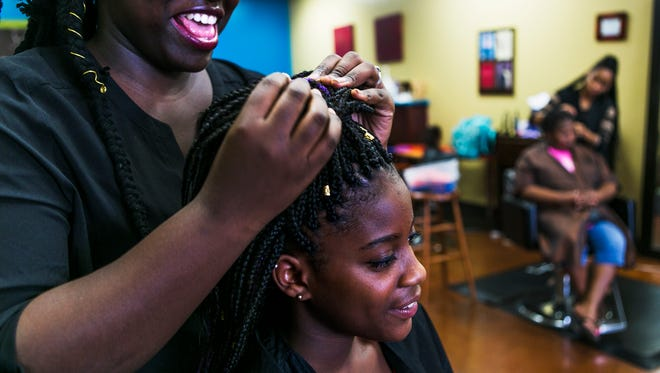 Angelina Liom, an apprentice from the Institute of Beauty, styles Dayah Brooks' hair into a fishtail during a session at A Natural Affair Beauty Lounge in East Memphis on Thursday. Takeisha Berry Brooks, owner of the salon, is accepting apprentices out of this new hair school located in Bartlett, which is the state's first natural hair school.