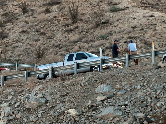 People sit on the highway railing while traffic is backed up for several turns in the uphill lane of Highway 74 following a vehicle collision near Vista Point which shut down the roadway on Wednesday afternoon, November 19, 2014 above Palm Desert, Calif.