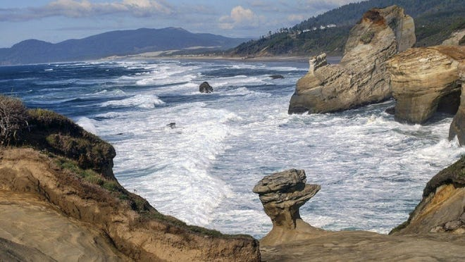 """This photo provided by Chelsea Rutherford shows a natural rock formation in Oct. 2008, at Cape Kiwanda State Natural Area which is a state park in Pacific City, Ore. The sandstone pedestal, which was found in pieces last week, was roughly 7 feet to 10 feet across and located in a fenced off section of the park. Oregon State Parks officials originally said they did not think the break at the site frequented by tourists was caused by humans but cellphone video captured a group of people knocking over the popular sandstone rock formation known as the """"Duckbill"""" on the Oregon beach. (Chelsea Rutherford/KATU News via AP)"""