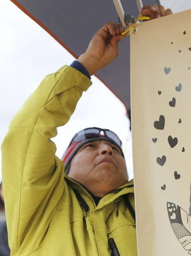Gary Mike hangs a banner that displays a photo his daughter, Ashlynne Mike, during an event to remember the 11-year-old on Saturday at the San Juan Chapter house.