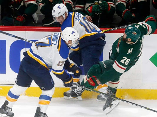 Minnesota Wild's Daniel Winnik, right, gets upended between St. Louis Blues' Jaden Schwartz, left, and Brayden Schenn in the first period of an NHL hockey game Tuesday, Feb. 27, 2018, in St. Paul, Minn. (AP Photo/Jim Mone)