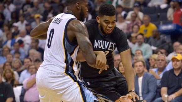 Minnesota Timberwolves forward Karl-Anthony Towns, right, drives against Memphis Grizzlies forward JaMychal Green (0) in the first half of an NBA basketball game Wednesday, Oct. 26, 2016, in Memphis, Tenn.